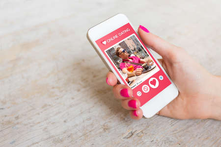 Photo for Woman using online dating app on mobile phone - Royalty Free Image