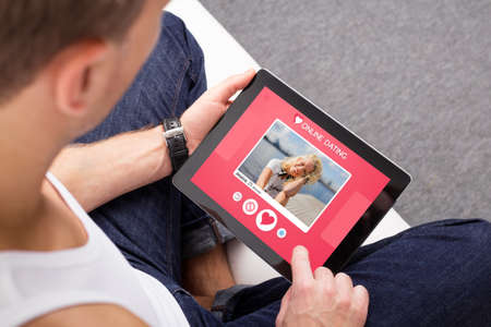 Photo for Man using online dating app on tablet - Royalty Free Image