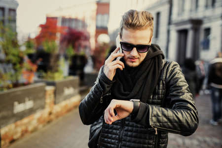 Photo for Man in the city talking on the phone and looking at smartwatch - Royalty Free Image