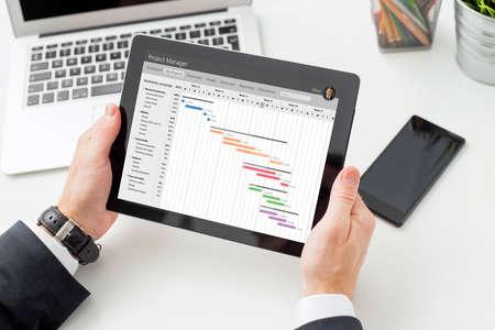 Photo pour Businessman looking at Gantt chart on tablet computer - image libre de droit