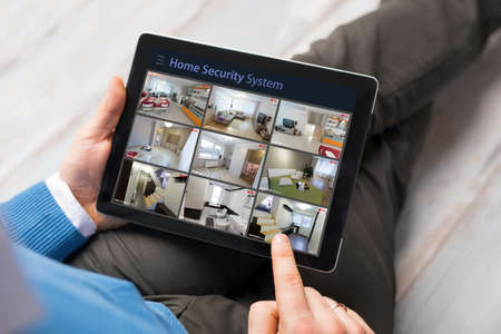 Photo pour Man looking at home security cameras on tablet computer - image libre de droit