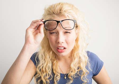 Foto de Woman with her glasses lifted up can't see - Imagen libre de derechos