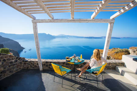 Photo for Woman enjoying breakfast with beautiful view over Santorini - Royalty Free Image