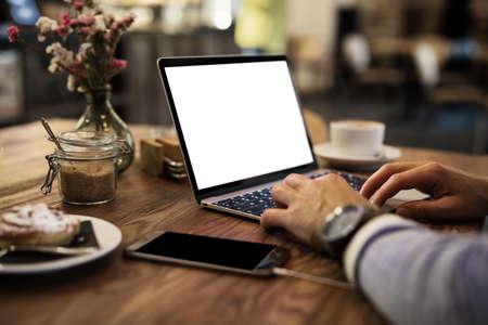 Photo pour Man using laptop in cafe - image libre de droit
