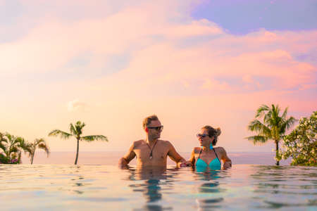 Photo pour Couple relaxing in infinity pool of exotic luxury resort - image libre de droit