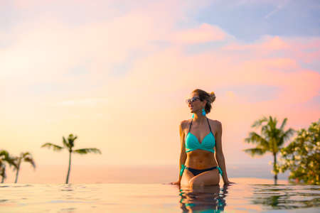 Photo pour Girl sitting on edge of infinity pool at beautiful sunset - image libre de droit