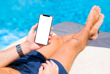 Photo for Man using mobile phone on vacation by the pool. Mobile phone mockup. - Royalty Free Image