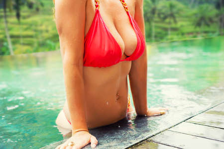 Photo pour Woman with big breasts in the pool - image libre de droit