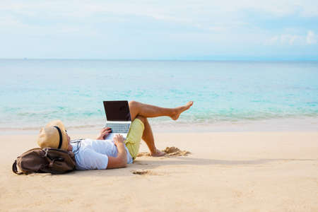 Photo pour Man working on laptop computer while relaxing on the beach - image libre de droit
