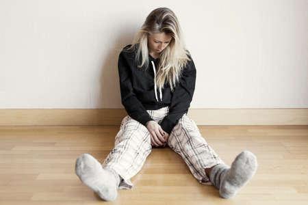 Foto de Desperate and sad woman sitting on floor - Imagen libre de derechos