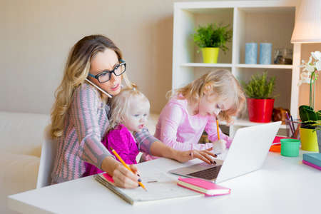 Photo pour Busy woman trying to work while babysitting two kids - image libre de droit