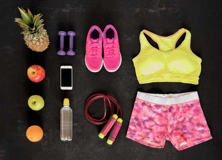 Fitness equipment objects flat lay on black floor