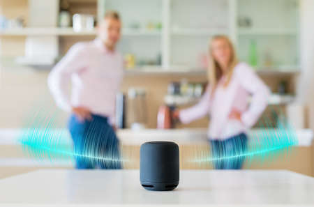 Photo pour Couple talking and listening to smart speaker at home - image libre de droit