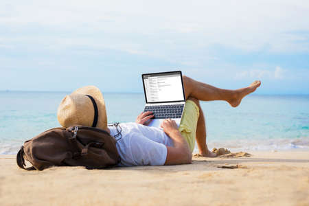 Photo pour Man reading email on laptop while relaxing on beach - image libre de droit