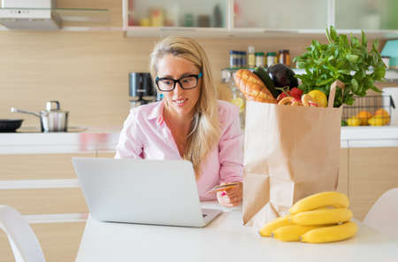 Photo pour Woman ordering groceries online - image libre de droit