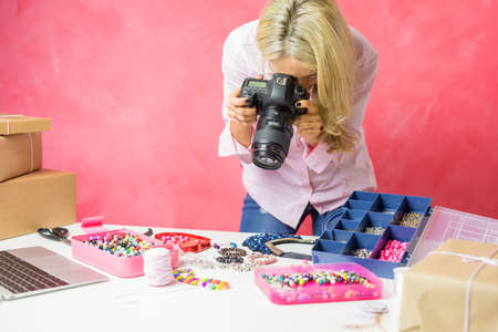 Photo pour Woman taking photos of her own created merchandise, sells them online and mails packages to buyers. - image libre de droit