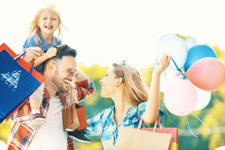 Photo pour Happy family walking along the street with shopping bags. - image libre de droit