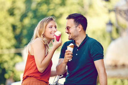 Photo for Portrait of happy young couple eating ice-cream in the city. - Royalty Free Image