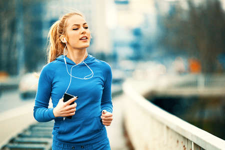 Photo for Young blonde woman is jogging on the bridge early in the morning. - Royalty Free Image