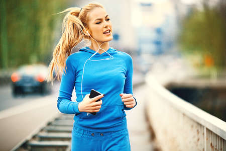 Foto de Young blonde woman is jogging on the bridge early in the morning. - Imagen libre de derechos