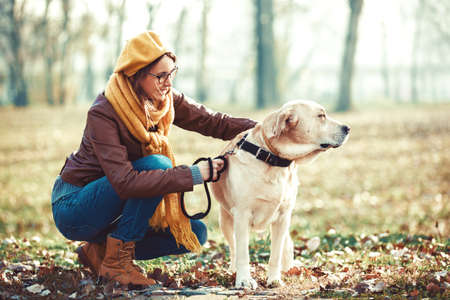 Photo pour Young woman enjoying autumn with her labrador. - image libre de droit
