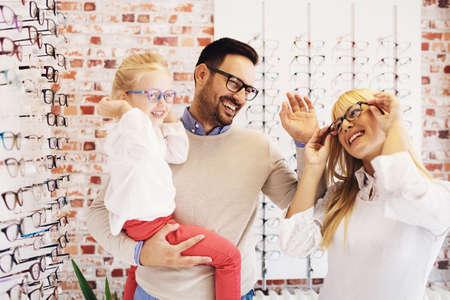 Photo pour Happy family choosing glasses in optics store. - image libre de droit