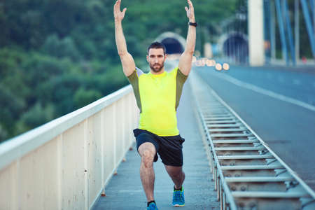 Photo pour Early morning workout. Handsome man exercising on the bridge. Living healthy lifestyle.  - image libre de droit