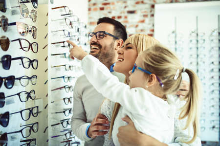 Photo pour Happy family choosing glasses in optics store. - image libre de droit