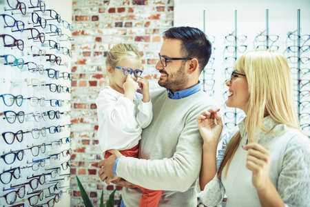 Photo for Happy family choosing glasses in optics store. - Royalty Free Image