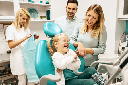 Photo for Dentist treating cute blonde child in his surgery. - Royalty Free Image