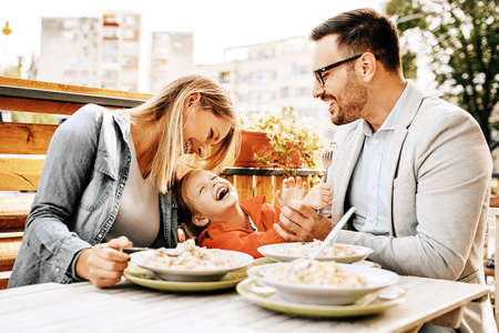 Photo pour Happy family is enjoying pasta in restaurant. - image libre de droit