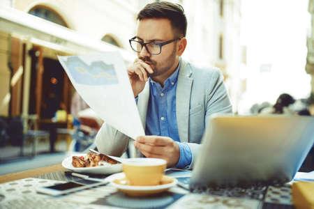 Foto de Businessman having breakfast and doing his work in cafe. - Imagen libre de derechos