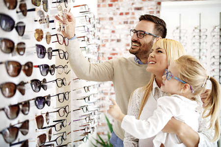 Photo pour Four year little girl in optics store choosing glasses with her father. Ophtamologist helping.  - image libre de droit