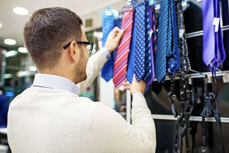 Foto für Portrait of handsome young man buying tie in the store. - Lizenzfreies Bild