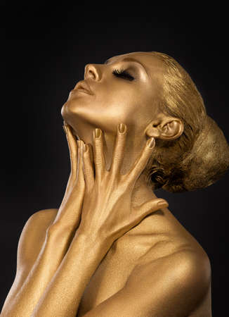 Coloring. Gilt. Golden Plated Woman's Face. Art concept. Gilded Body. Focus on her hands