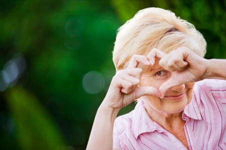 Photo pour Positivity. Happy Funny Senior Woman Showing Symbol of Heart - image libre de droit