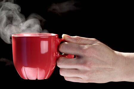 Little red tea cup in woman hand isolated over black background
