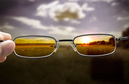 Photo pour out of focus nature at sunset with hand holding a glasses that correct the vision - image libre de droit