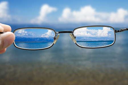 Foto de blurry vision of a seashore on a beautiful summer day and a hand holding a pair of glasses that correct the vision - Imagen libre de derechos