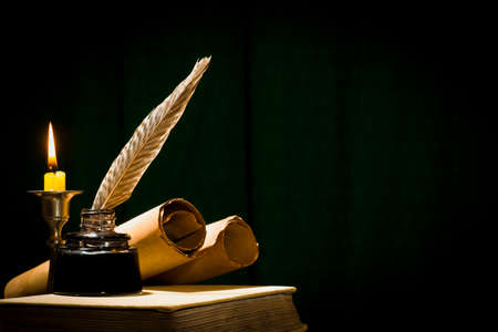 Foto de The concept of education and writing, a pen in an inkwell and a candle with a candle, and a book on a dark background. - Imagen libre de derechos