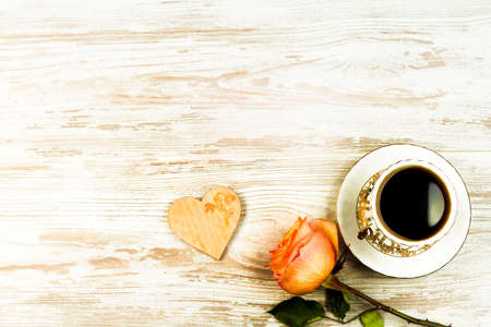 Photo for A cup of coffee, and an orange rose and heart on a background of vintage boards - Royalty Free Image
