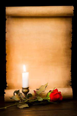 Photo pour A scroll of old parchment, a red rose and a lit candle - image libre de droit