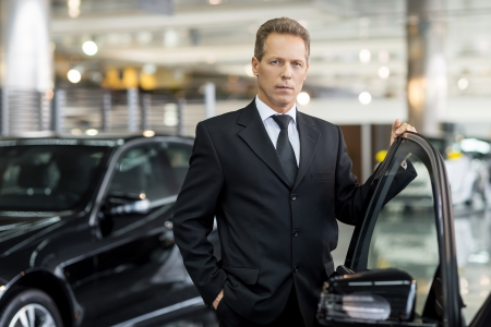 Photo pour Confident in his choice. Confident grey hair man in formalwear holding hand on opened car door and looking at camera - image libre de droit
