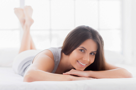 What a pleasure to do nothing! Attractive young smiling woman lying in bed and looking at camera