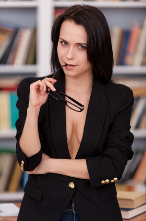 Photo pour Confident and sexy teacher. Beautiful young woman in suit over the naked body holding glasses and looking at camera while standing against book shelf  - image libre de droit