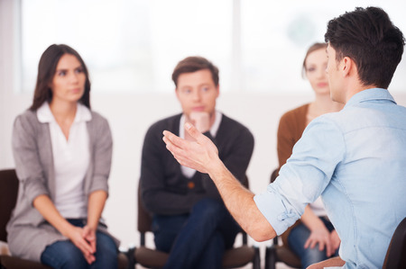 Photo pour Sharing his problems with people. view of man telling something and gesturing while group of people sitting in front of him and listening - image libre de droit