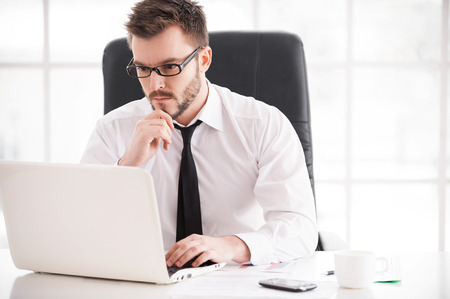 Photo for Businessman at work. Handsome young beard man in shirt and tie working on laptop while sitting at his working place - Royalty Free Image