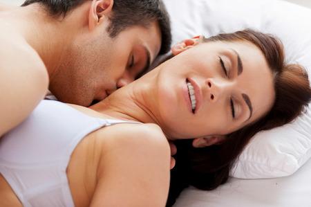 Foto de I love him kissing me! Beautiful young loving couple having sex while lying in bed - Imagen libre de derechos