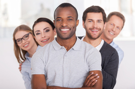 Photo for Confident business team. Cheerful young African man keeping arms crossed and smiling while group of people standing behind him in a row and looking at camera - Royalty Free Image
