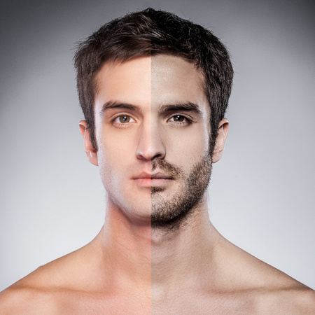 Foto de Handsome young man with half shaved face looking at camera while standing against grey background - Imagen libre de derechos